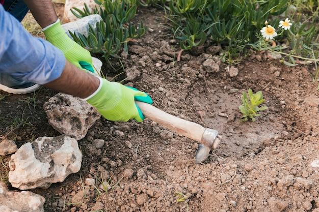 Une vue aérienne de la main de l'homme creusant le sol avec une houe