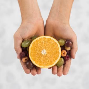 Une vue aérienne de la main d'une personne tenant orange coupée en deux avec des raisins et framboises