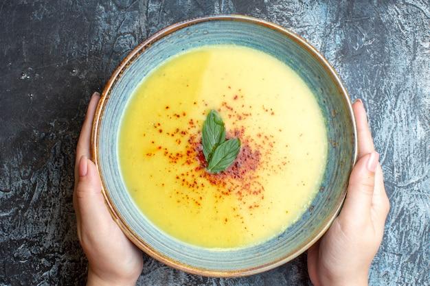 Vue aérienne de la main tenant un pot bleu avec une soupe savoureuse sur fond bleu