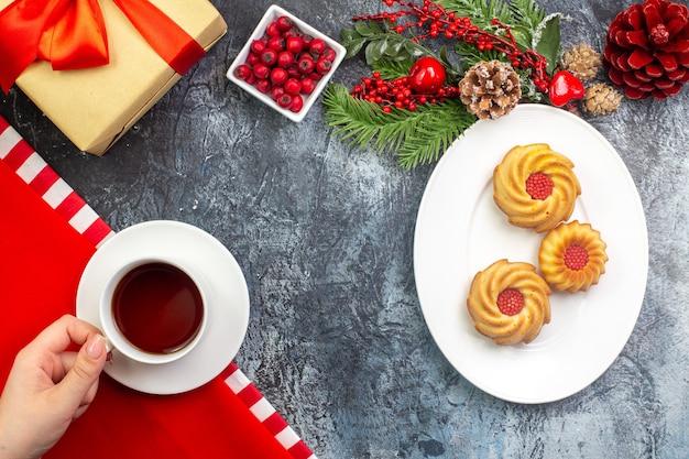 Vue aérienne d'une main tenant une tasse de thé noir, une serviette rouge et des biscuits d'une assiette blanche, cadeau d'accessoires du nouvel an avec un ruban rouge sur une surface sombre