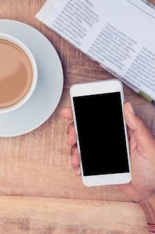 Vue aérienne de la main tenant un téléphone intelligent par café et journal sur la table