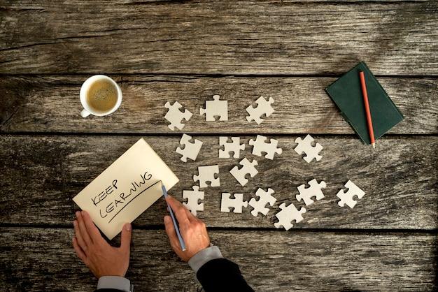 Vue aérienne des mains d'un homme d'affaires qui écrit continue d'apprendre la note sur un bureau en bois à côté de pièces de puzzle.