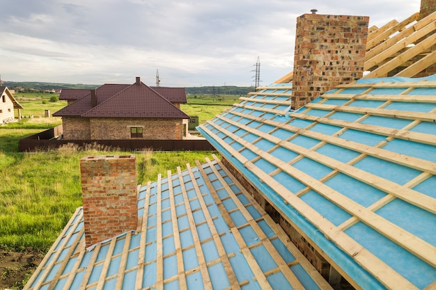 Vue aérienne d'une maison en brique avec charpente en bois en construction.
