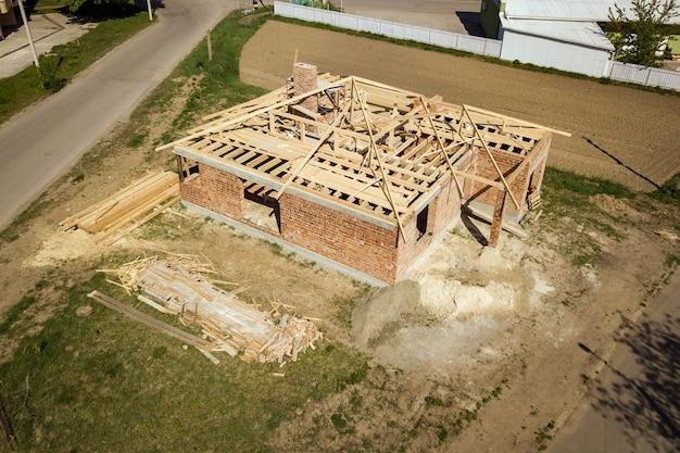 Vue aérienne de la maison en brique inachevée avec structure à ossature de toit en bois en construction.