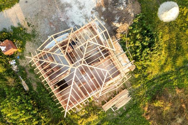 Vue aérienne de la maison en brique inachevée avec structure de toit en bois en construction.