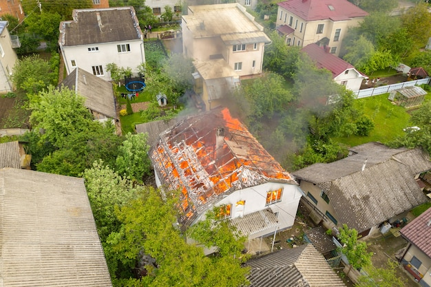 Vue aérienne d'une maison en feu avec flammes orange et fumée épaisse blanche