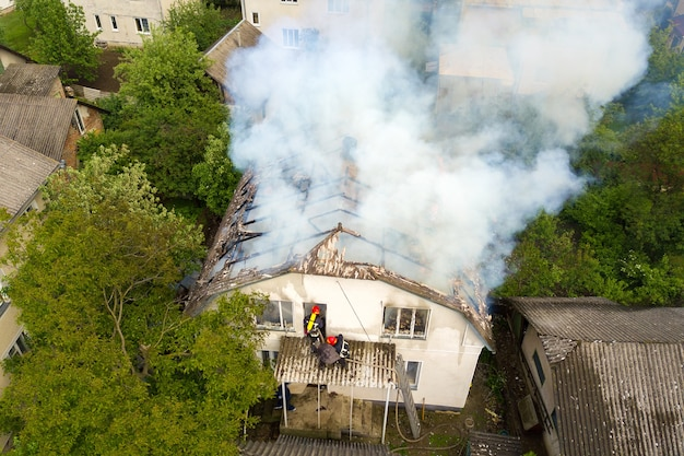 Vue aérienne d'une maison en feu avec des flammes orange et une fumée épaisse blanche.
