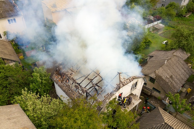 Vue aérienne d'une maison en feu avec des flammes oranges et une épaisse fumée blanche.