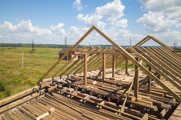 Vue aérienne de la maison inachevée avec structure à ossature de toit en bois en construction.