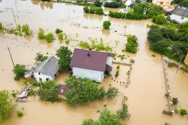 Vue aérienne d'une maison inondée avec de l'eau sale tout autour.
