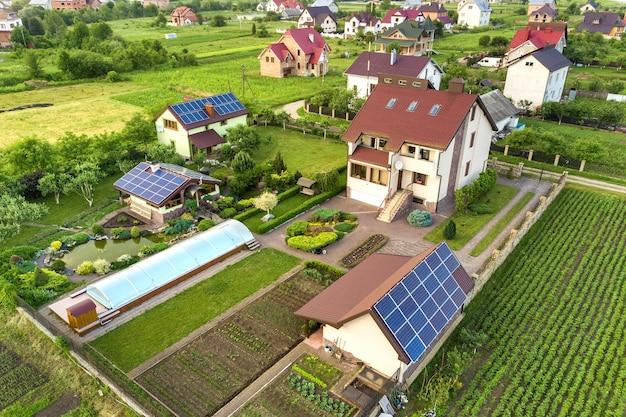 Vue aérienne d'une maison privée en été avec des panneaux photovoltaïques solaires bleu sur le toit et la cour verte