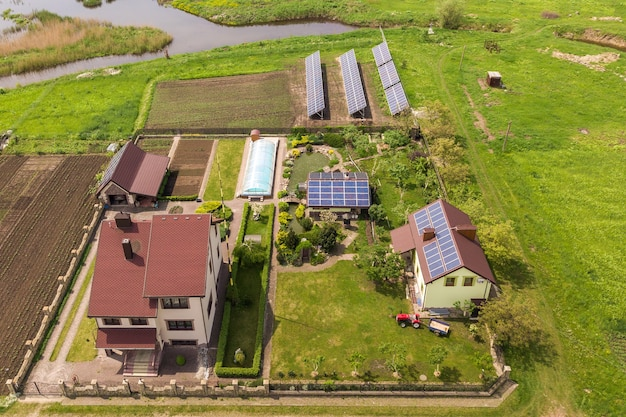 Vue aérienne d'une maison privée en été avec des panneaux photovoltaïques solaires bleus sur le toit et dans la cour.
