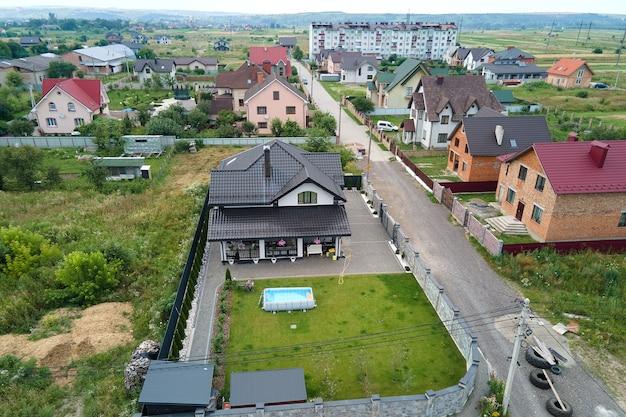 Vue aérienne de la maison privée avec jardin verdoyant et petite piscine sur pelouse.