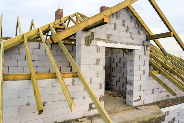 Vue aérienne d'une maison privée avec murs en briques de béton cellulaire et charpente en bois pour le futur toit.