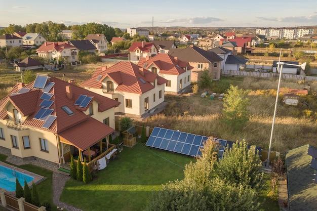 Vue aérienne d'une maison privée résidentielle avec des panneaux solaires sur le toit et une éolienne.