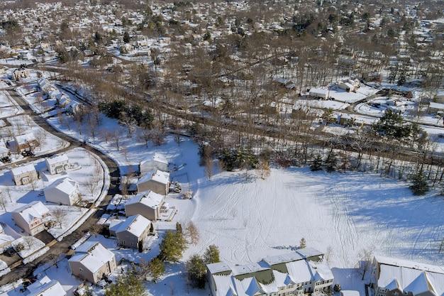 Vue aérienne de maisons d'habitation couvertes de neige en hiver avec de la neige sur les maisons couvertes et les routes.