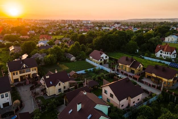 Vue aérienne de maisons d'habitation en zone rurale suburbaine au coucher du soleil.