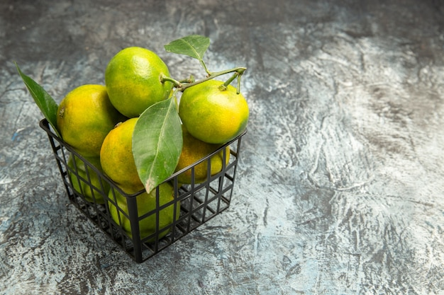 Vue aérienne de mandarines vertes avec des feuilles dans un panier sur fond gris