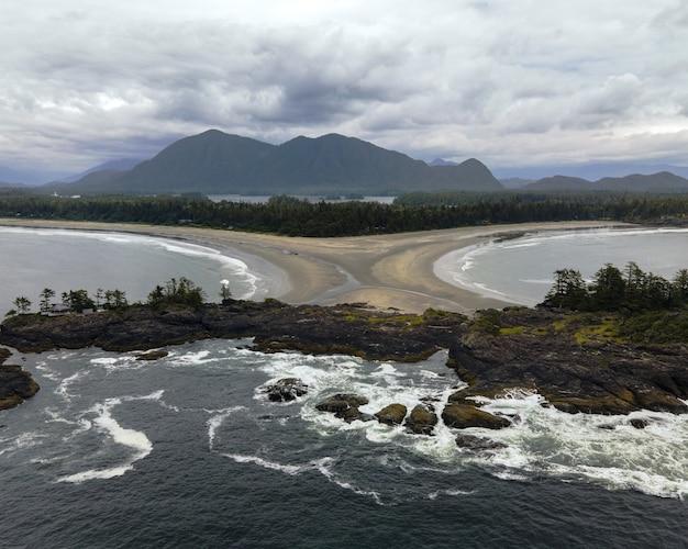 Vue aérienne d'une mer entourée de rochers avec des montagnes derrière
