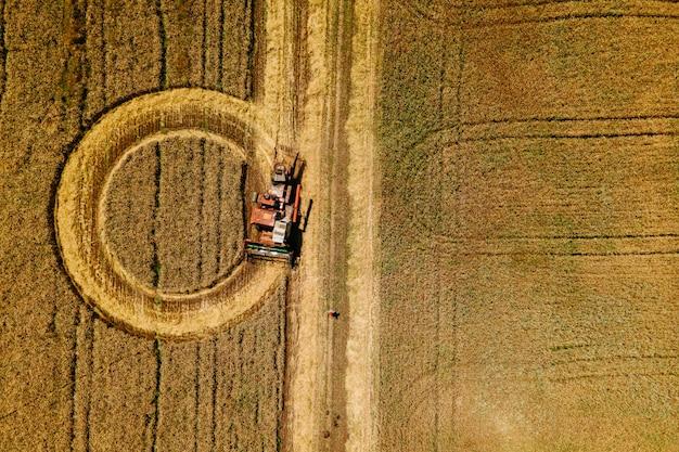 La vue aérienne de la moissonneuse-batteuse crée des cercles sur une image du temps de récolte du champ de blé k d'en haut