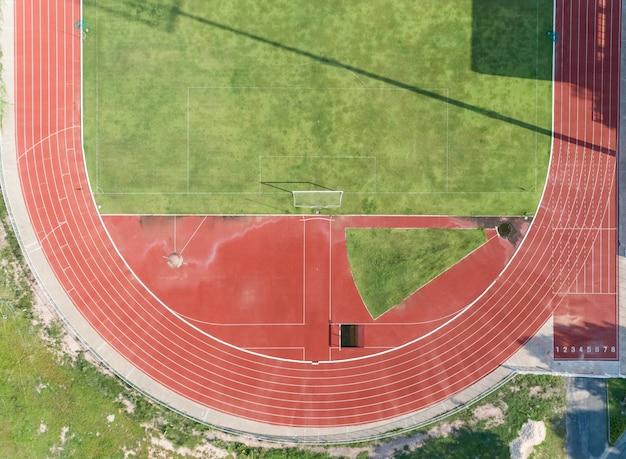 Vue aérienne sur la moitié du terrain de football, terrain de football avec numéros sur piste de course rouge.