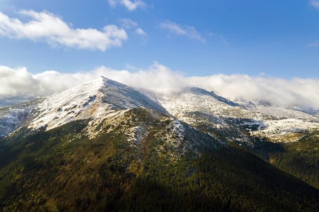 Vue aérienne de montagnes majestueuses couvertes de forêt d'épinettes vertes et de hauts sommets enneigés.