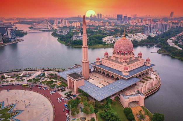 Vue aérienne de la mosquée de putra avec le centre-ville de putrajaya au coucher du soleil en malaisie
