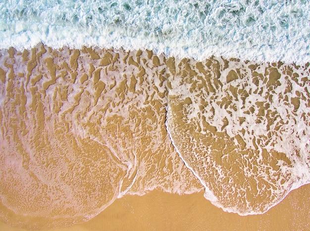 Vue aérienne de la mousse des vagues de la mer avec du sable orange et de l'eau verte