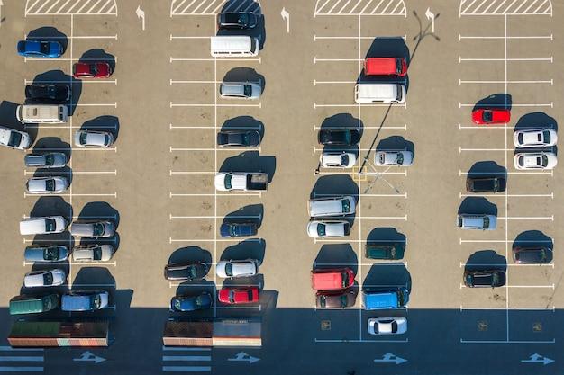 Vue aérienne de nombreuses voitures colorées garées sur un parking avec des lignes et des marquages