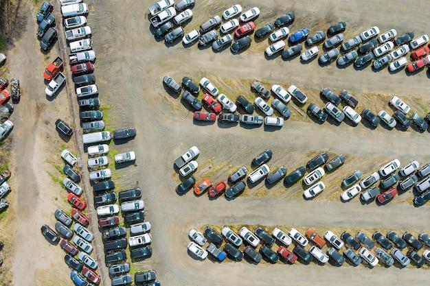 Vue aérienne de nombreux lots de vente aux enchères de voitures d'occasion garées distribuées dans un parking.
