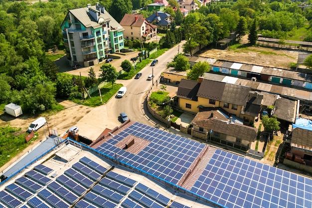 Vue aérienne de nombreux panneaux solaires photovoltaïques montés sur le toit d'un bâtiment industriel.