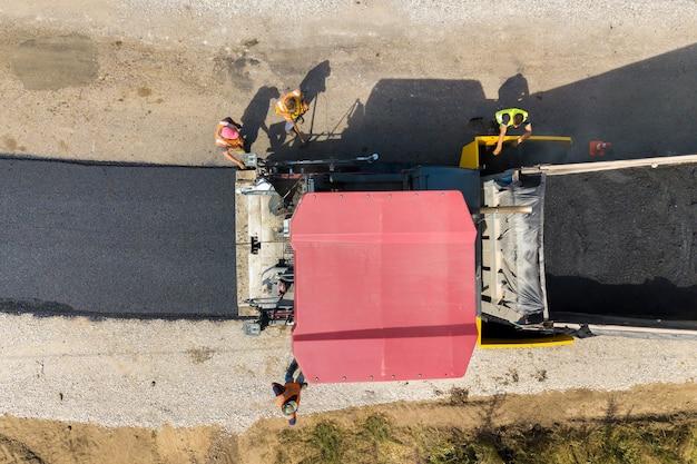 Vue aérienne de la nouvelle construction de routes avec des machines de pose d'asphalte au travail.