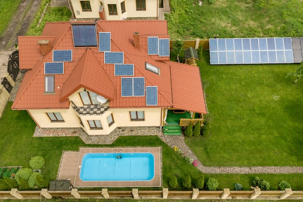 Vue aérienne d'une nouvelle maison autonome avec panneaux solaires et radiateurs de chauffage à eau sur le toit et cour verte avec piscine bleue.