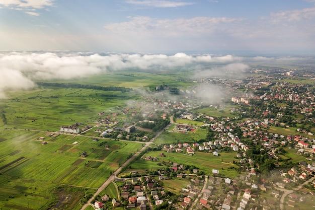 Vue aérienne de nuages blancs au-dessus d'une ville ou d'un village avec des rangées de bâtiments et des rues sinueuses entre les champs verts en été. paysage de campagne d'en haut.