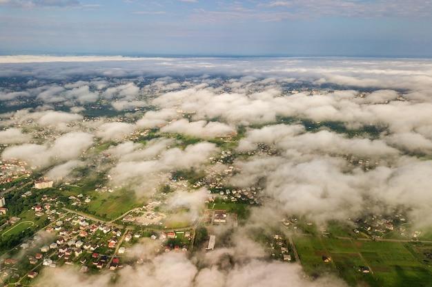 Vue aérienne de nuages blancs au-dessus d'une ville ou d'un village avec des rangées de bâtiments et des rues sinueuses