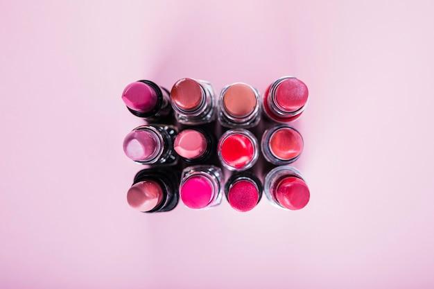 Vue aérienne o différents rouges à lèvres colorés sur une surface rose