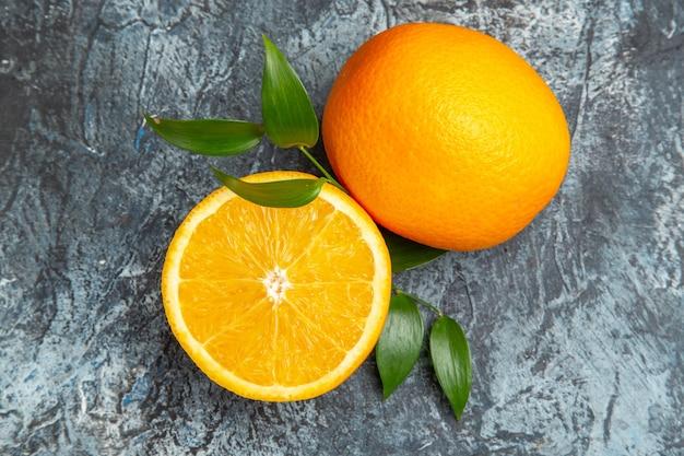 Vue aérienne de l'orange fraîche coupée en deux et entière avec des feuilles sur fond gris photo stock