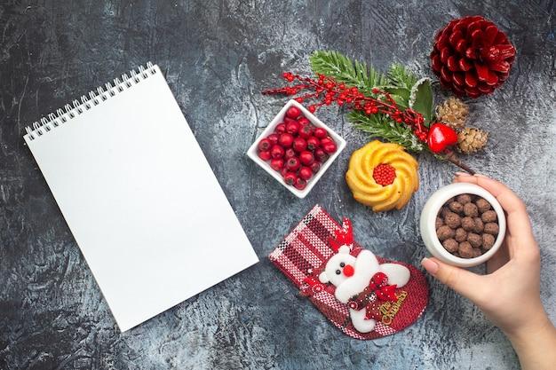 Vue aérienne d'un ordinateur portable délicieux accessoire de décoration de biscuits santa claus chaussette et cornell dans un bol de branches de sapin sur une surface sombre