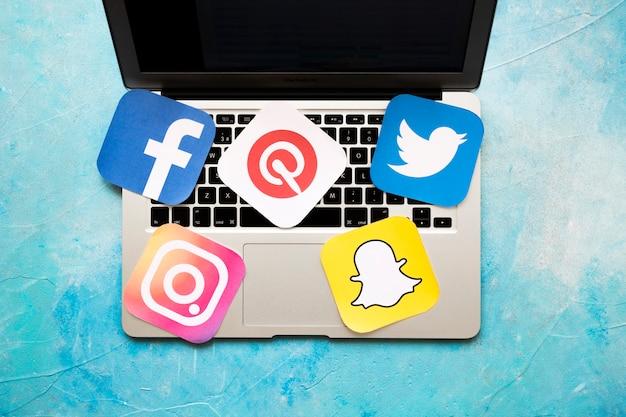 Vue aérienne de l'ordinateur portable avec des icônes de medic social sur le fond bleu