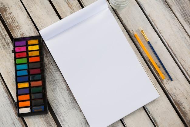 Vue aérienne de la palette colorée, pinceau, crayon et livre sur la surface en bois