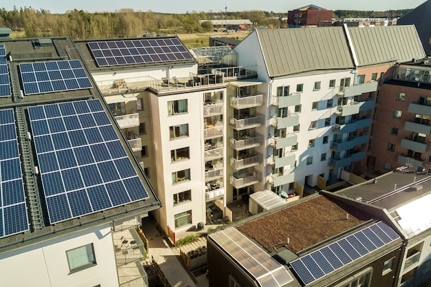 Vue aérienne de panneaux solaires photovoltaïques sur un toit d'un bloc de construction résidentiel pour produire de l'énergie électrique propre.