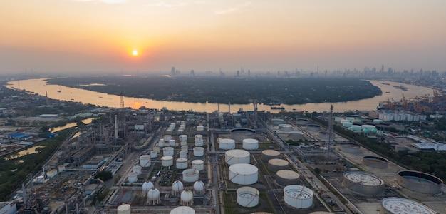 Vue aérienne panoramique sur la raffinerie de pétrole et la rivière au crépuscule.