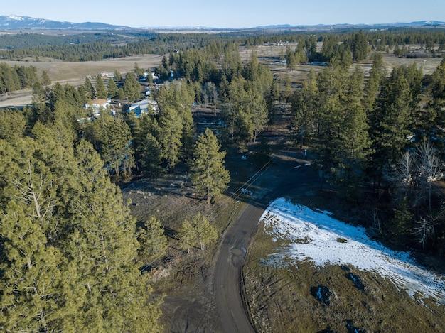 Vue aérienne d'un paysage forestier avec une route de campagne sous la lumière du soleil