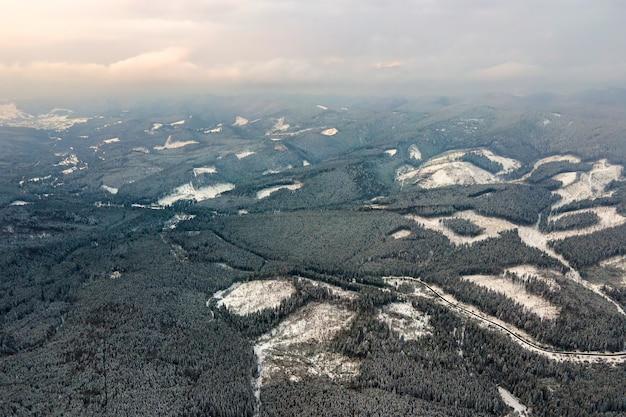 Vue aérienne d'un paysage d'hiver aride avec des collines montagneuses couvertes d'une forêt de pins à feuilles persistantes après de fortes chutes de neige par une soirée froide et calme.