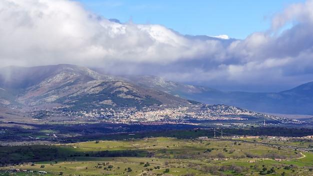 Vue aérienne paysage de montagne verte avec des nuages sombres et des villages avec des maisons à flanc de montagne. navacerrada madrid. l'europe .