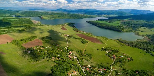 Vue aérienne des paysages verdoyants, des champs et d'une rivière sous le ciel nuageux par une journée ensoleillée