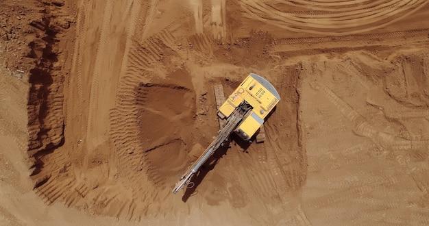 Vue aérienne d'une pelleteuse, pelle sur chenilles au travail sur une construction.