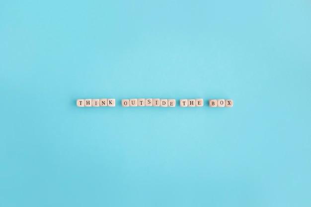 Vue aérienne de penser en dehors du texte de la boîte faite avec de petits blocs sur fond bleu