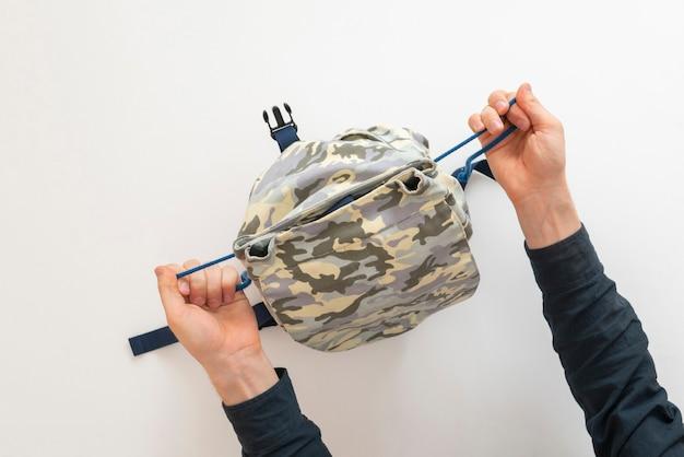 Une vue aérienne de la personne emballant des choses dans le sac avant le début du voyage