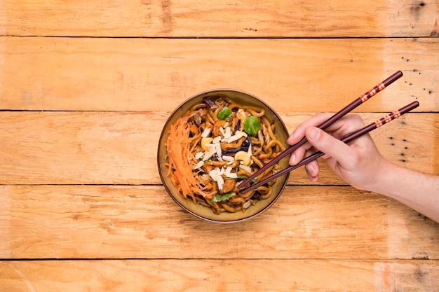 Une vue aérienne d'une personne qui ramasse les nouilles avec des baguettes sur la table